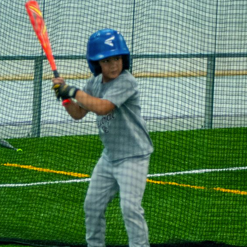 Boy holding the bat about to hit the baseball