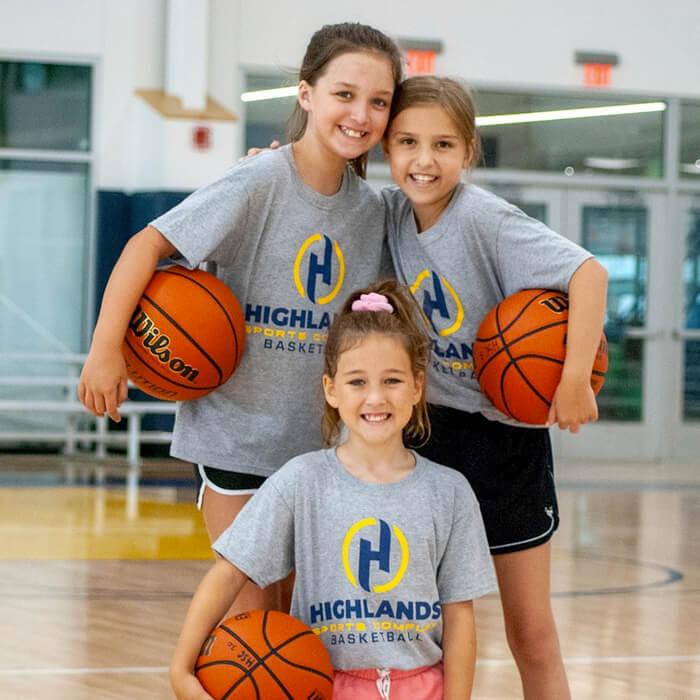 Three girls holding basketballs