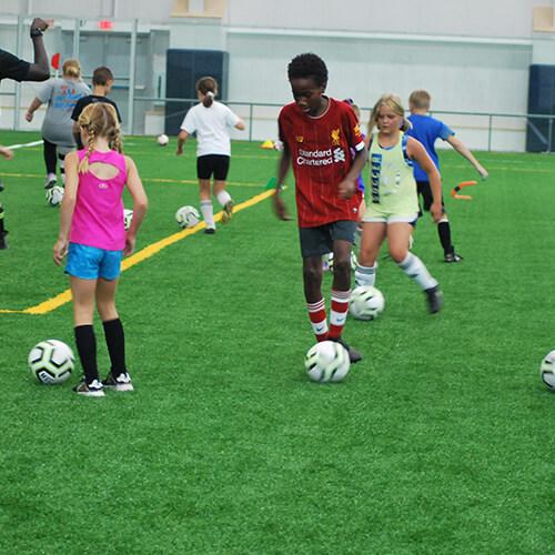 People kicking soccer balls