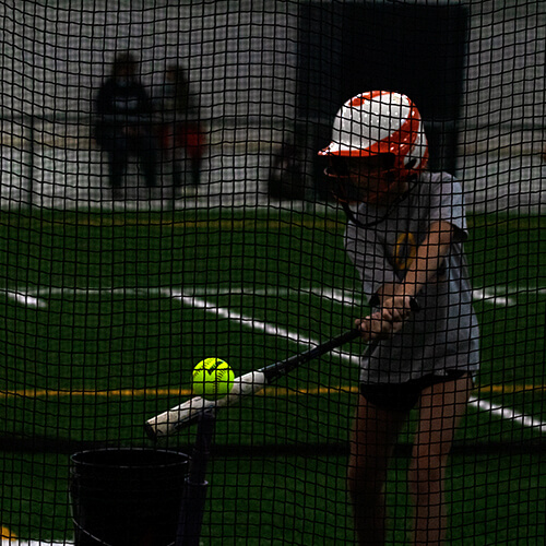 Girl holding a softball bat trying to hit the softball