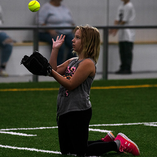 Girl about to catch a soft ball