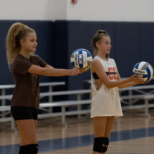 Two girls holding volleyballs