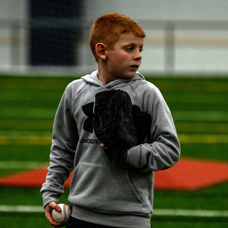 Person that has a glove in one hand and in the other a baseball