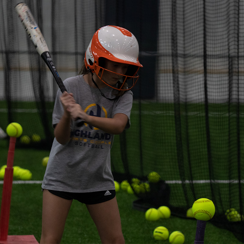 Person holding bat ready to hit the ball