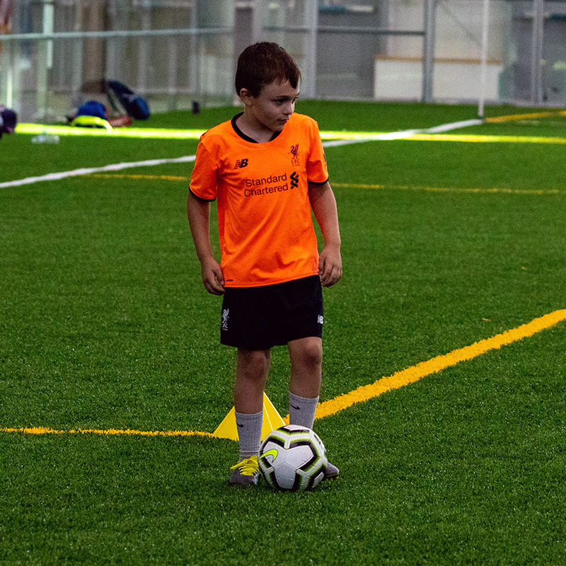 Person in a orange shirt kicking the ball